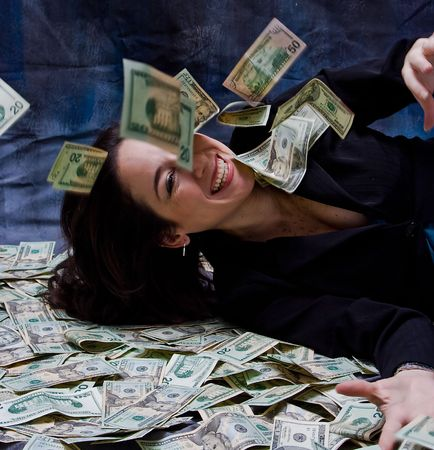 Rich business woman waving laying with her money, she smiles as money falls out of the sky, isolated on a dark background Stock Photo