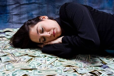 as: Rich business woman laying with her money as she dreams about it isolated on a dark background
