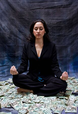 meditates: Rich woman meditating while sitting in money isolated on a dark background