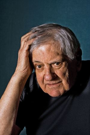 Dramatic portrait of a senior man with his hand on the side of his face and in his hair wearing a black shirt isolated on grayblue photo