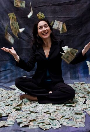 sit: Rich woman sitting with open arms in money and as money falls out of the sky isolated on a dark background