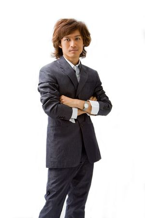Young Asian business man dressed in a gray pinstripe suit with arms crossed, isolated