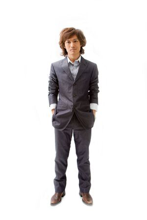 Young Asian business man dressed in a gray pinstripe suit with hands in pockets, isolated Reklamní fotografie - 3420899