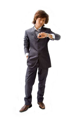 Young Asian business man dressed in a gray pinstripe suit with hand in pocket and looking at his watch, isolated