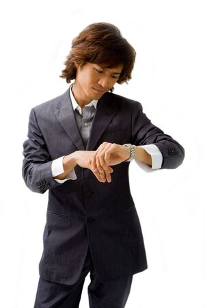 Young Asian business man dressed in a gray pinstripe suit checking time by looking at his watch, isolated