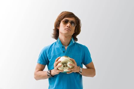 Sporty Asian guy in blue t-shirt holding a small golden soccer ball with both hands, isolated Reklamní fotografie - 3450460