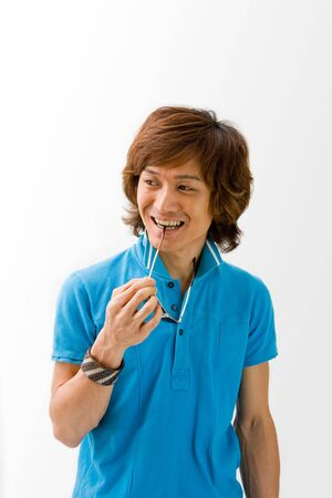 Smiling Asian guy in blue t-shirt holding sunglasses and biting on it, isolated