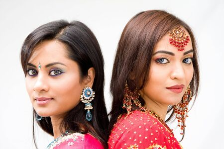 Two beautiful Bengali brides in colorful dresses, isolated photo