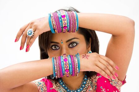 Beautiful face of a Bengali bride with her arms across her head covered with colorful bracelets, isolated