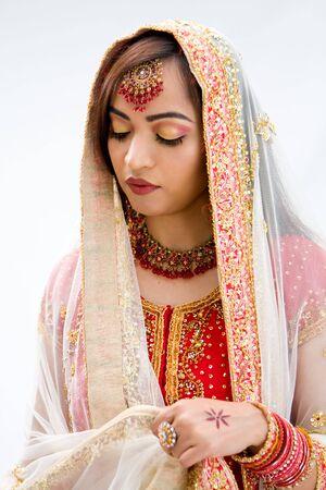 Elegant Bengali bride arranging veil looking down, isolated photo