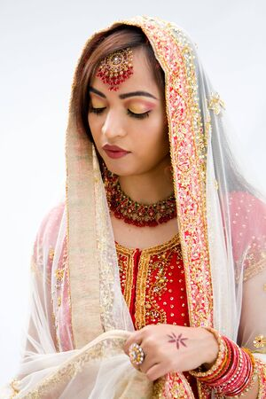 pakistani females: Elegant Bengali bride arranging veil looking down, isolated Stock Photo