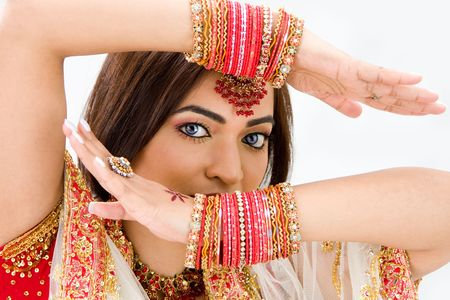 Beautiful face of a Bengali bride with her arms across her head covered with colorful bracelets, isolated photo