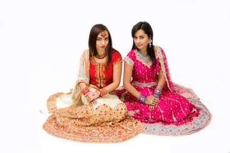 Two beautiful harem girls or belly dancers or Hindu brides sitting, isolated photo