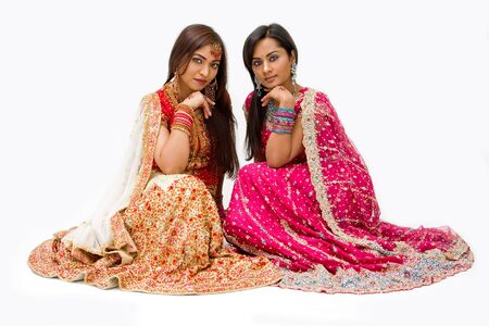 pakistani females: Two beautiful harem girls or belly dancers or Hindu brides sitting, isolated