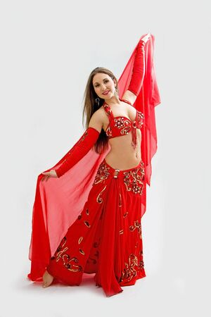 Beautiful belly dancer in red outfit holding veil, isolated