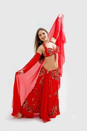Mooie buik danseres in rode outfit die sluier, geïsoleerd  Stockfoto