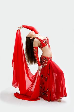 Beautiful belly dancer in red outfit holding veil hanging backward, isolated