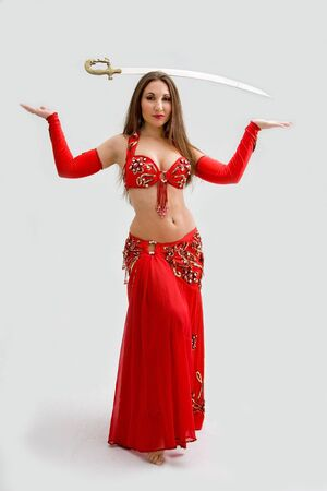 Beautiful belly dancer in red outfit with sword on her head, isolated photo