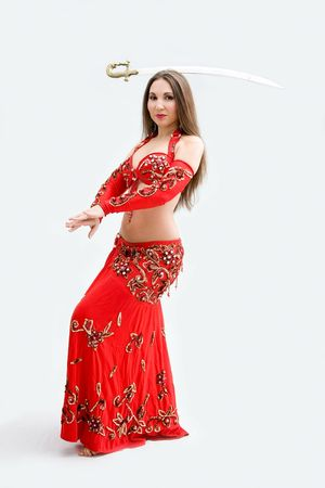 Beautiful belly dancer in red outfit balancing sword, isolated photo