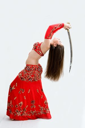 Beautiful belly dancer in red outfit holding sword hanging backward, isolated