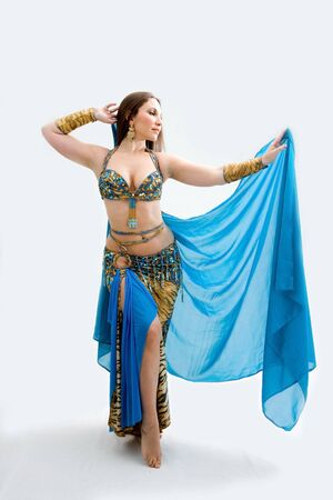 Beautiful belly dancer in blue outfit holding veil, isolated