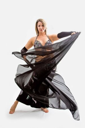 Beautiful belly dancer in black outfit holding veil, isolated photo