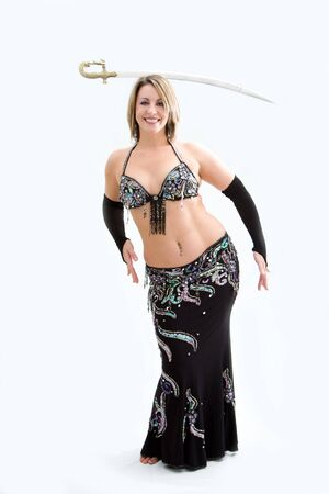 Beautiful belly dancer in black outfit balancing sword, isolated photo
