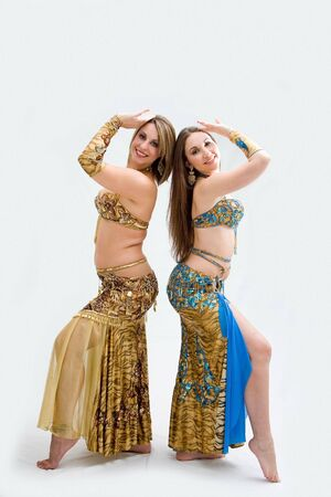 sexy girl dance: Two beautiful belly dancers dressed in gold and blue, isolated