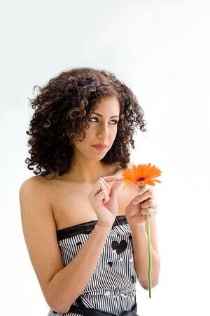 wild hair: Bella giovane donna bruna con capelli ricci selvatici e arancio fiore in mano tirando petali, isolati Archivio Fotografico