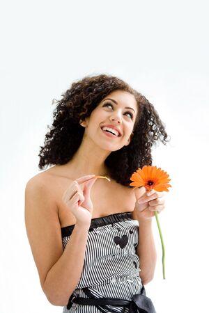 wild hair: Sorridendo felice bella giovane donna bruna con capelli ricci selvatici e fiori d'arancia in mano e tirando petali, isolati Archivio Fotografico