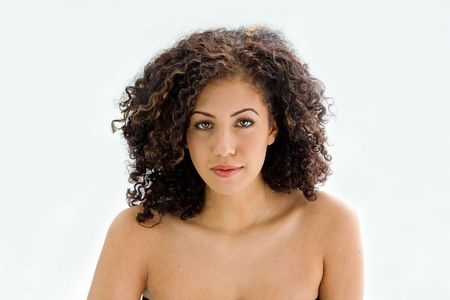 bare shoulders: Sincere beautiful young woman with brown curly wild hair and bare shoulders, isolated Stock Photo