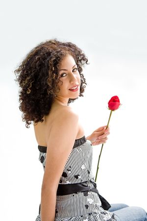 sincere: Sincere beautiful young woman with brown curly wild hair and bare shoulders holding red rose, isolated