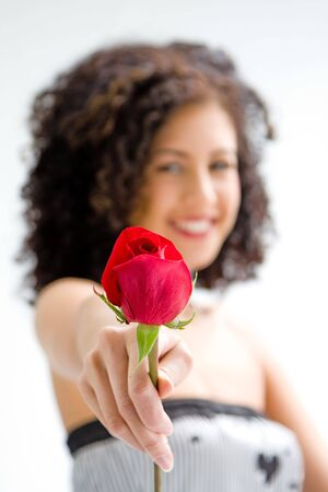 strapless: Sincere beautiful young woman with brown curly wild hair and bare shoulders presenting red rose, isolated Stock Photo