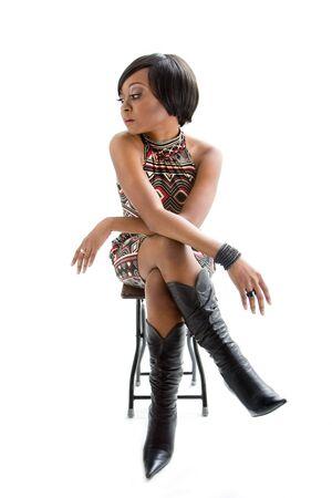 """escabeau: Belle femme africaine dans le style """"seventies"""" assis sur un tabouret et en regardant � gauche, isol�e Banque d'images"""