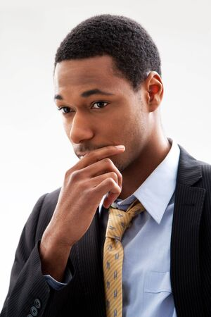 pondering: Handsome African American male in blue shirt and yellow tie and black pinstripe blazer, isolated Stock Photo