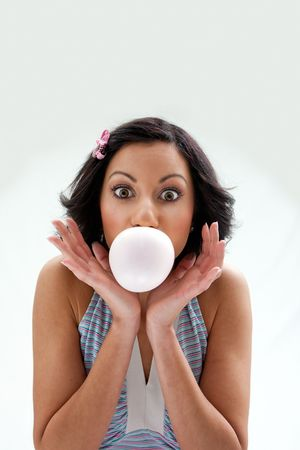 Beautiful Latina girl with huge eyes open blowing a bubblegum bubble, isolated photo
