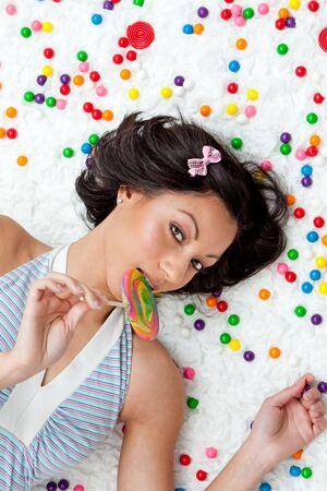 Young Latina woman laying on ruffled cloud like floor between colorful bubblegum balls eating a lollipop photo