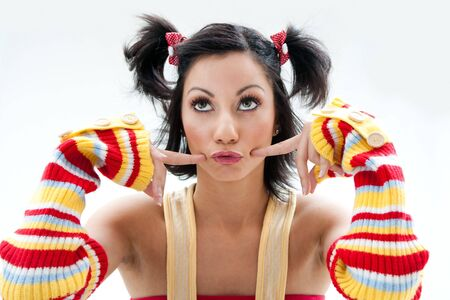 ponytails: Beautiful fun latina girl with bright colored arm warmers and ponytails with red ribbons in her hair looking up, isolated