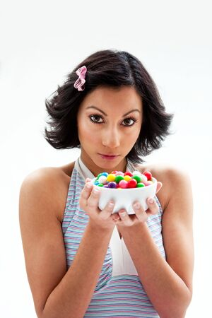 Happy beautiful candy girl with a bowl of colorful bubblegum candy balls, isolated photo