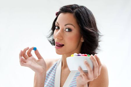 Happy beautiful candy girl with a bowl of colorful bubblegum candy balls licking her lip, isolated photo