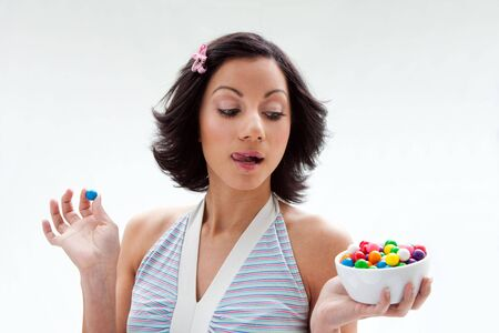 Happy beautiful candy girl with a bowl of colorful bubblegum candy balls licking her lip, isolated Stock Photo - 4193251