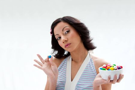 Happy beautiful candy girl with a bowl of colorful bubblegum candy balls thinking, isolated photo