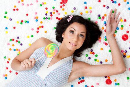 bubblegum: Young Latina woman laying on ruffled cloud like floor between colorful bubblegum balls holding a lollipop