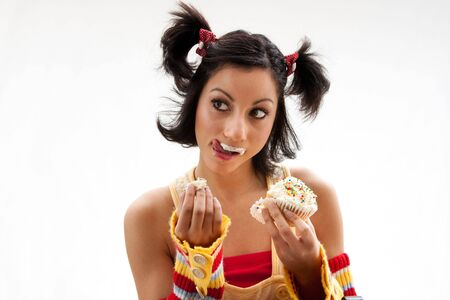 Beautiful Latina girl eating a cupcake with her fingers and licking her icing covered lip, isolated photo