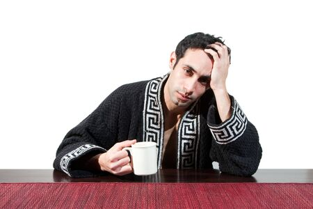 recovering: Handsome guy in the morning who just woke up sitting at a table in his robe with a cup recovering from his hangover, isolated on white Stock Photo