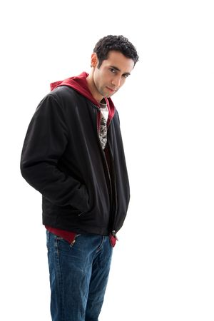 Cool handsome mischievous male wearing a red hoodie, black coat and jeans, with hands in pocket and head down, isolated Stock Photo