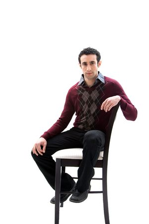 Handsome guy wearing business casual clothes sitting on a high chair, isolated