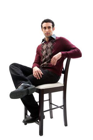 Elegant man dragen van zakelijke casual kleren vergadering over een hoge stoel met de benen overschreden en bewapenen rust, geïsoleerd