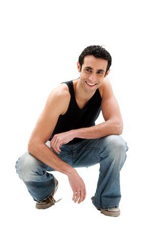 squatting: Chico guapo sonriente C�ucaso llevar negro mangas y vaqueros en cuclillas, aisladas