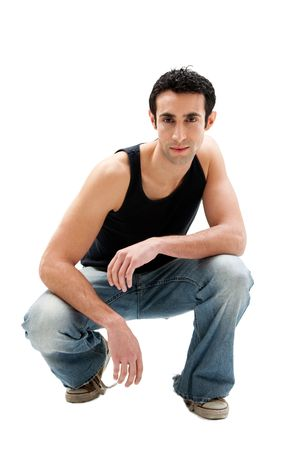 Handsome serious Caucasian guy wearing black tank top and jeans squatting, isolated photo